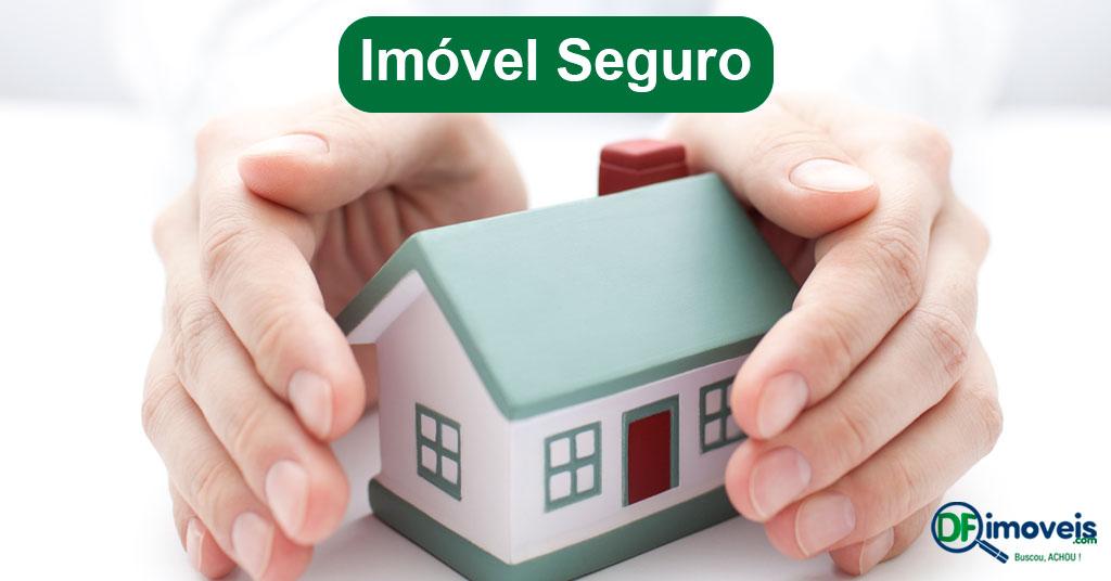 Imagem de uma casa pequena protegida por mãos, significando segurança. Acima a frase Imóvel Seguro